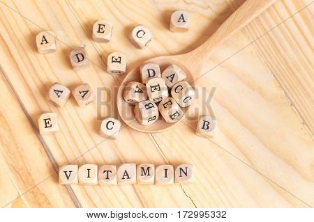 Top views vitamin word made from wooden letters on the table and A B C D E on the wood spoon Health concept