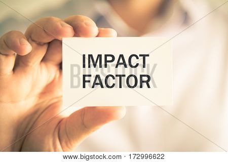 Businessman Holding Impact Factor Message Card