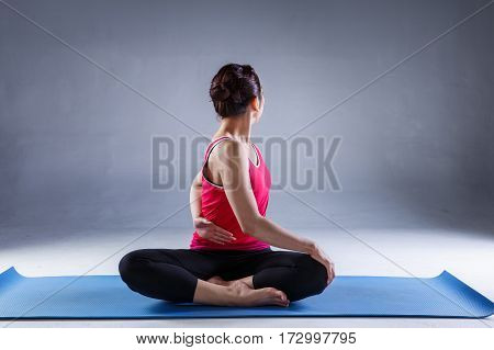 Portrait of gorgeous young woman practicing yoga in studio with on dark background woman seeking enlightenment through meditationrelaxed girl performing yoga routine