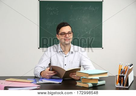 Handsome young teacher sitting at table in classroom