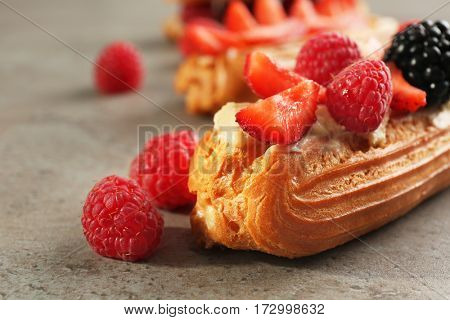 Delicious eclair with berries on light textured background