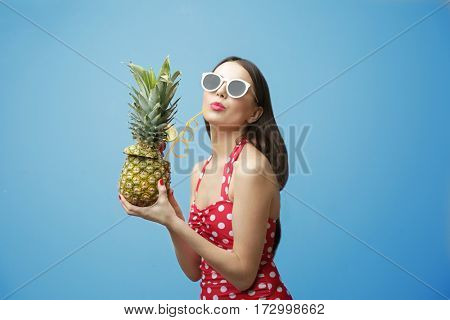 Young beautiful woman with cocktail in pineapple on light background