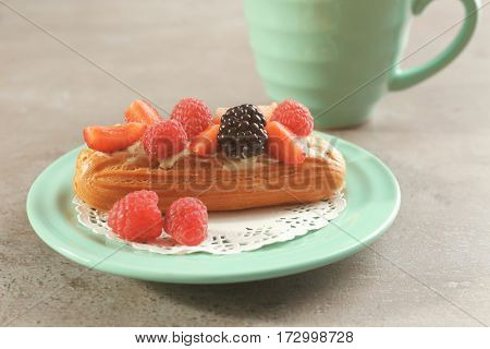 Green plate with delicious eclairs, berries and doily on light textured background