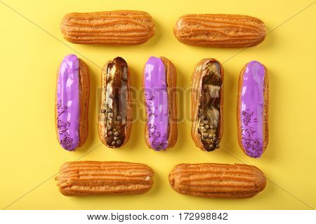 Delicious eclairs on yellow background