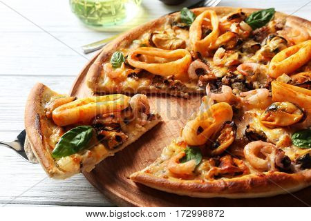 Tasty sliced pizza with seafood on wooden tray