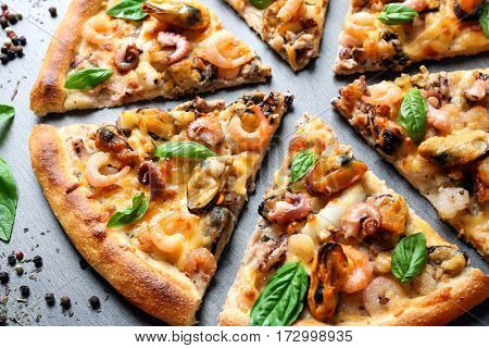 Cutting fresh seafood pizza on grey background