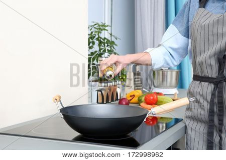 Woman pouring oil in pan at kitchen