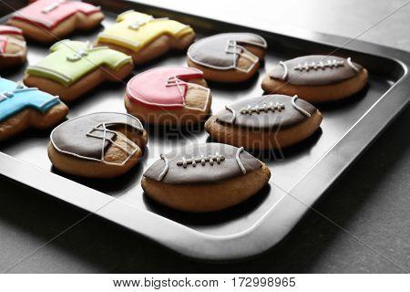 Football cookies on baking tray, closeup