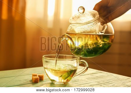 Hand pouring tea from glass teapot into a cup