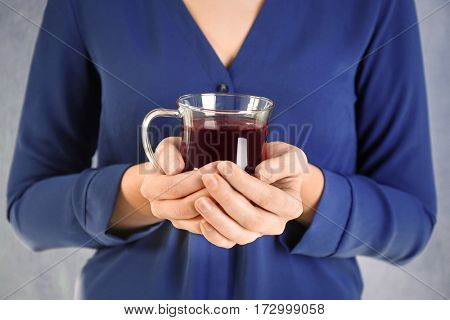 Young woman holding cup of tea, closeup