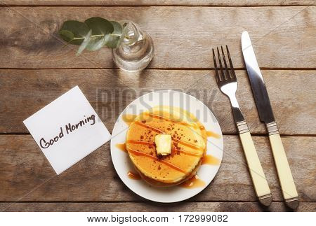 Delicious breakfast and GOOD MORNING greeting note on wooden table, top view