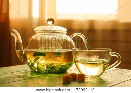 Glass teapot and cup of herbal tea on wooden table