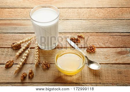 Composition with milk and honey on wooden background