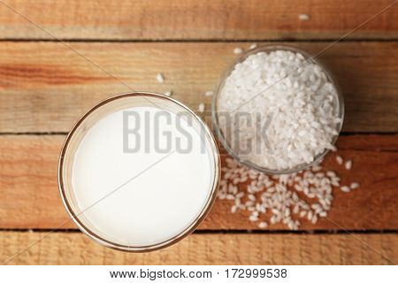 Glass of tasty rice milk on wooden table
