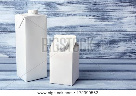 Two simple milk boxes on wooden background