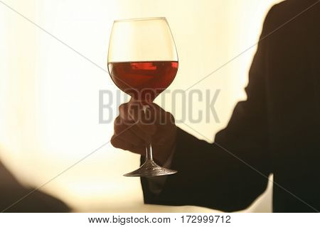 Man holding glass with wine on blurred background
