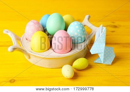 Easter bunny with colorful eggs on wooden table