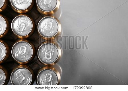 Cans of beer on gray table, top view