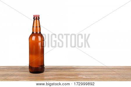 Bottle of beer on table against white background