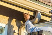 Worker Attaching Aluminum Rain Gutter and Down Spout to Fascia of House. poster