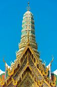 Beautiful Asian style architecture. Lavishly decorated roof and stupa of building in Grand Palace. Bangkok Thailand poster