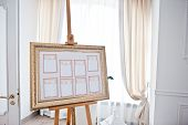 Wedding seating chart on the easel at light restaurant. poster