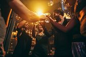 Low angle shot of group of friends enjoying drinks at bar together. Young people at nightclub toasting cocktails. poster