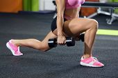 Beautiful sportive woman training with dumbbell in gym poster