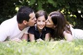 Happiness and harmony in family life. Happy family concept. Young mother and father kissing their daughter in the park. Happy family resting together on the green grass. Family having fun outdoor poster