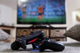 Playing video game. Console controllers or joysticks. Football or soccer game on the television. Widescreen tv stands on commode.