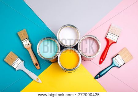 Four Open Cans Of Paint With Brushes On Bright Background. Yellow, White, Pink, Turquoise Colors Of