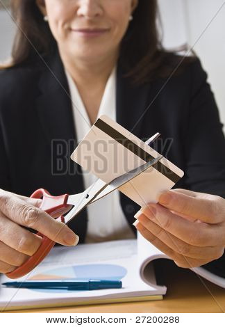 A businesswoman is cutting up a credit card with a pair of scissors.  Vertically framed shot.