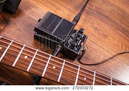 Black Electric Guitar With Equipment And Accessories, Audio Stomp Box Effects And Cables In Music St