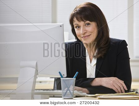 Attractive business woman stting at desk behind computer monitor smiling at camera. Horizontal.