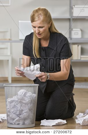 A businesswoman is on the floor in an office and is lookign through the trash.  She is looking away from the camera.  Vertically framed shot.