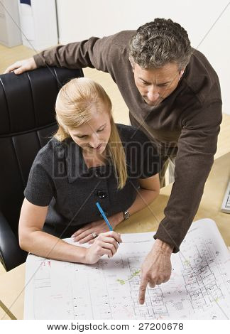 A man and a woman are working together on some blueprints in an office.  Vertically framed shot.