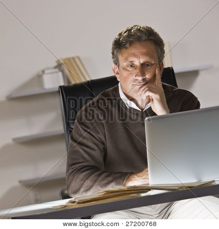 A businessman is working on a laptop in an office.  He is looking away from the camera.  Square framed shot.