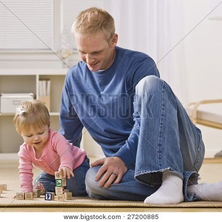 A young father is on the floor playing with his daughter.  He is smiling and looking at her.  Square framed shot.