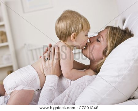 A beautiful young mother kissing her baby.  Horizontally framed shot.