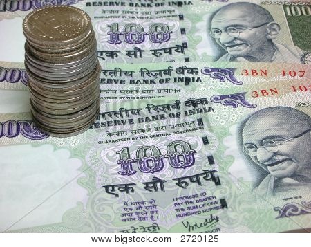 Three one hundred Indian rupee Notes / bills and a coin stack poster
