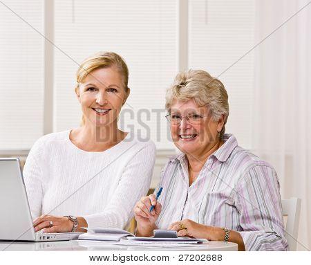 Senior woman writing checks with daughter help