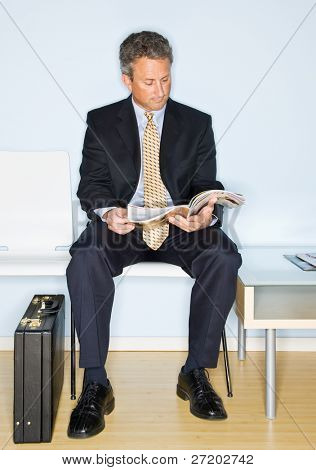 Businessman reading magazine in waiting room