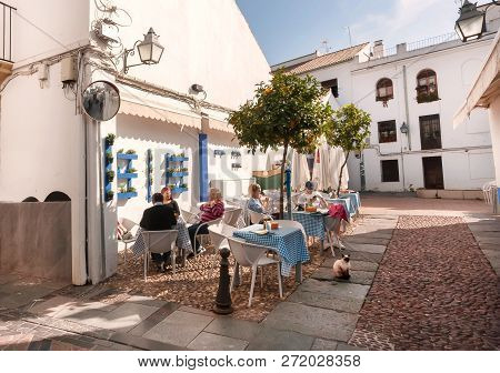 Cordoba, Spaine - Nov 17: Relaxing People Having Dinner On Historical Street Of Town In Andalusia On