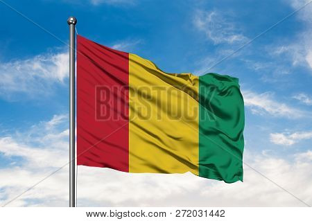 Flag Of Guinea Waving In The Wind Against White Cloudy Blue Sky. Guinean Flag.