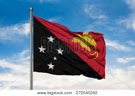 Flag Of Papua New Guinea Waving In The Wind Against White Cloudy Blue Sky. Guinean Flag.