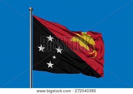 Flag Of Papua New Guinea Waving In The Wind Against Deep Blue Sky. Guinean Flag.