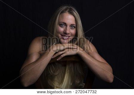 Beautiful Woman Portrait Taken In Low Light With An Orange Top