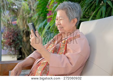 Asian Elder Woman Holding Mobile Phone At Home. Elderly Senior Using Smartphone In Garden