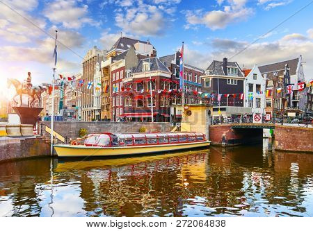 Amsterdam Channel, Netherlands. Traditional dutch houses, bridge and touristic pleasure boat on water. Statue of equestrian of Queen Wilhelmina on steed. Sunset street, decorated with flags.
