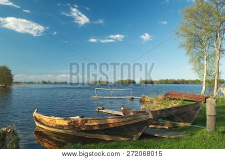 Wooden Boats. The Boats Are Moored To The Pier. The Boats Are Used To Fishing In The Lake.